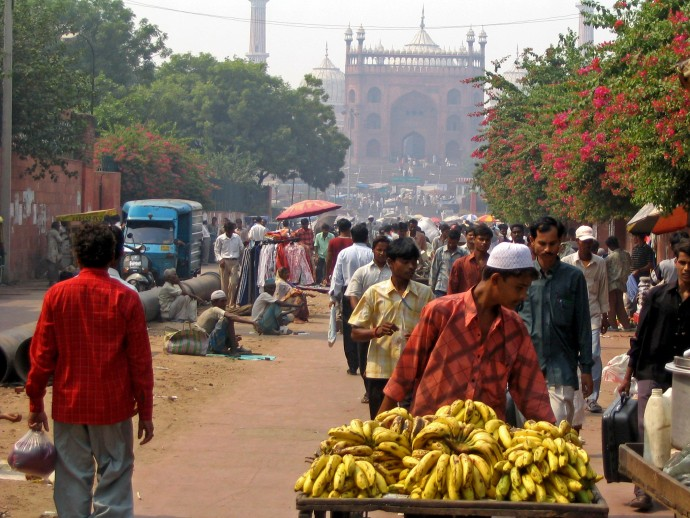 boy selling bananas in india in front of a mosque