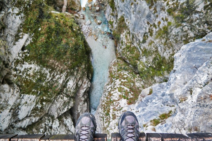 hiking-shoes-on-bridge-above-river