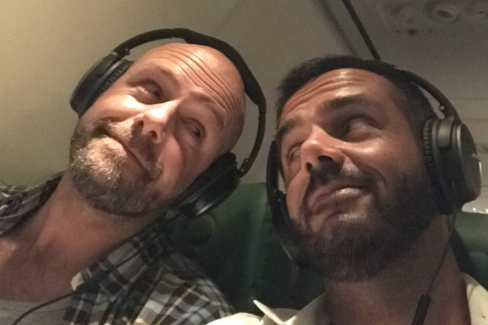 gay couple travel bloggers use noise cancelling headphones Bose Quiet comfort